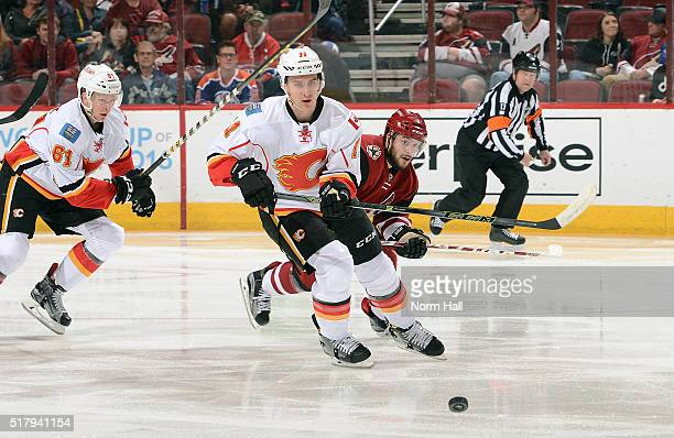 Mikael Backlund of the Calgary Flames passes the puck away from Tobias Rieder of the Arizona Coyotes during the first period at Gila River Arena on...