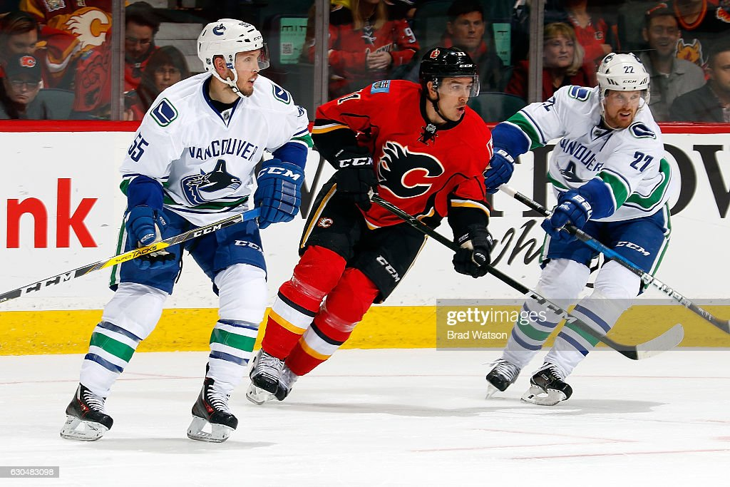 Mikael Backlund #11 of the Calgary Flames skates against Alex Biega #55 and Daniel Sedin #22 of the Vancouver Canucks during an NHL game on December 23, 2016 at the Scotiabank Saddledome in Calgary, Alberta, Canada.