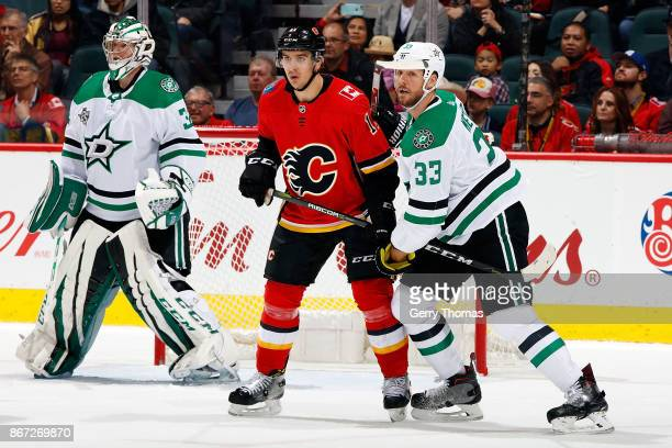 Mikael Backlund of the Calgary Flames skates against Marc Methot of the Dallas Stars during an NHL game on October 27 2017 at the Scotiabank...