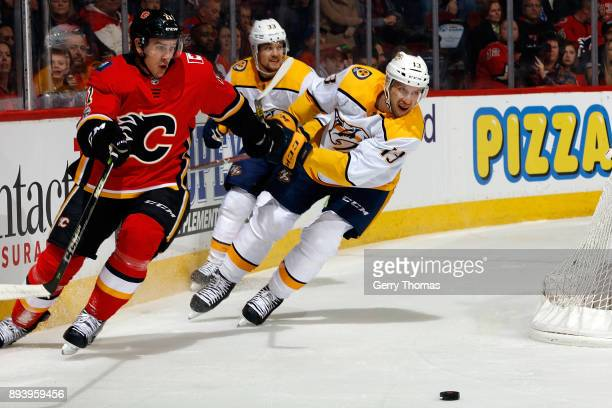 Mikael Backlund of the Calgary Flames skates against Nick Bonino of the Nashville Predators during an NHL game on December 16 2017 at the Scotiabank...