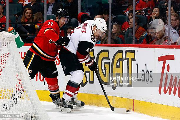 Mikael Backlund of the Calgary Flames skates against Zbynek Michalek of the Arizona Coyotes during an NHL game at Scotiabank Saddledome on March 11...