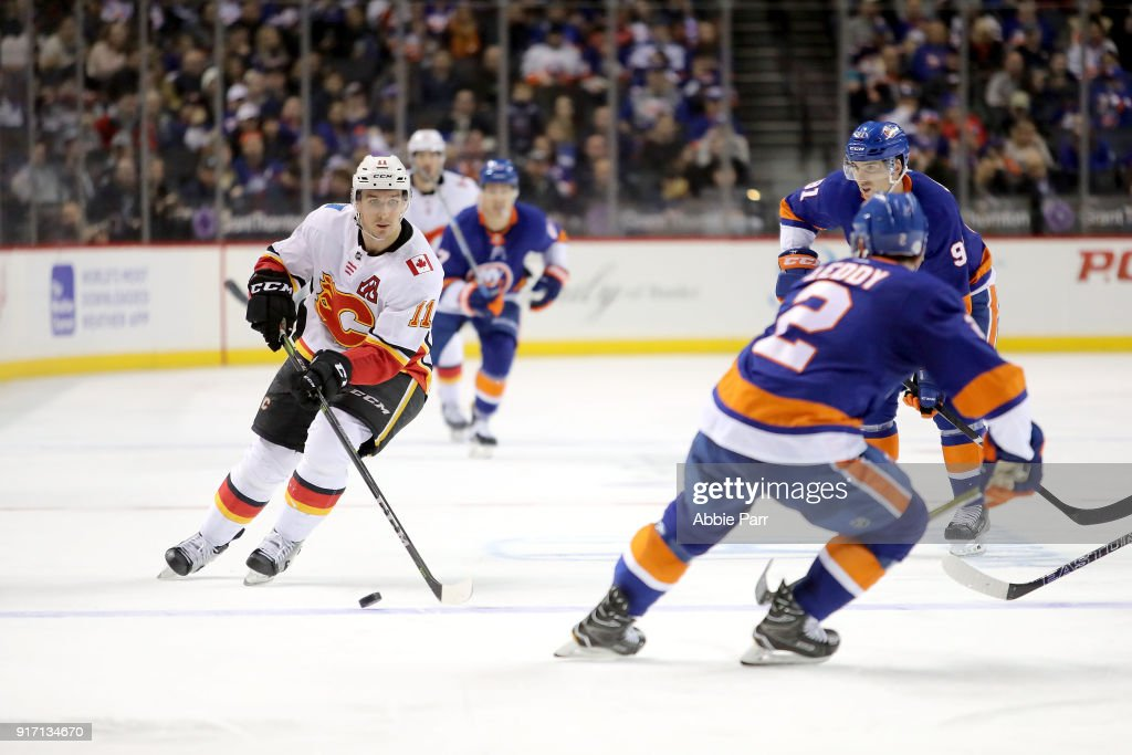 Mikael Backlund #11 of the Calgary Flames skates with the puck against Nick Leddy #2 of the New York Islanders in the third period during their game at Barclays Center on February 11, 2018 in the Brooklyn borough of New York City.