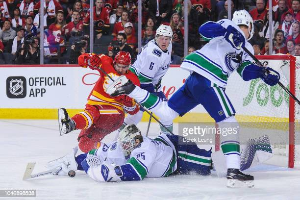 Mikael Backlund of the Calgary Flames takes a shot on Jacob Markstrom of the Vancouver Canucks during an NHL game at Scotiabank Saddledome on October...