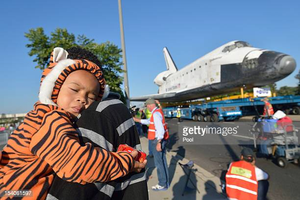 Mikael Ector tries to get some rest as his dad Michael Ector checks out NASA Space Shuttle Endeavour as it arrives at the Forum enroute to the...
