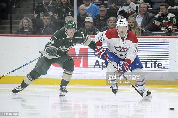Mikael Granlund of the Minnesota Wild and Alexei Emelin of the Montreal Canadiens skate after the puck during the second period of the game on...
