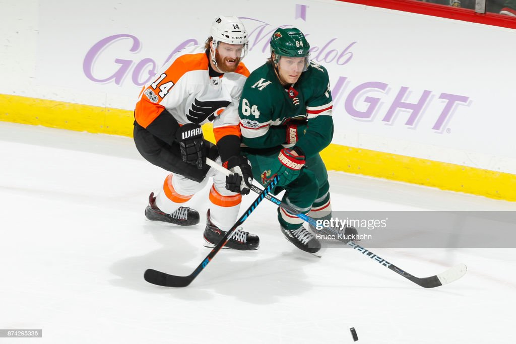 Mikael Granlund #64 of the Minnesota Wild and Sean Couturier #14 of the Philadelphia Flyers skate to the puck during the game at the Xcel Energy Center on November 14, 2017 in St. Paul, Minnesota.