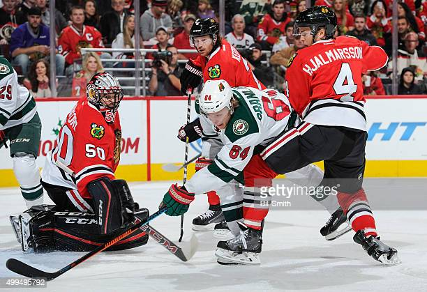 Mikael Granlund of the Minnesota Wild assists on a goal against goalie Corey Crawford of the Chicago Blackhawks as Niklas Hjalmarsson defends in the...