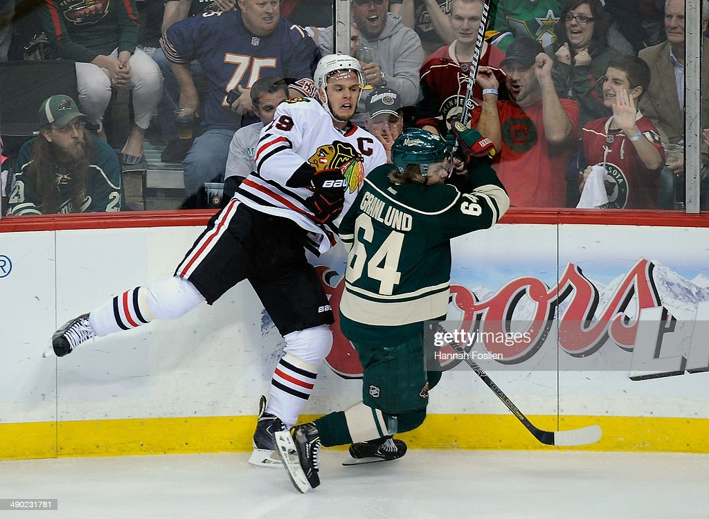 Mikael Granlund #64 of the Minnesota Wild checks Jonathan Toews #19 of the Chicago Blackhawks into the boards during the first period in Game Six of the Second Round of the 2014 NHL Stanley Cup Playoffs on May 13, 2014 at Xcel Energy Center in St Paul, Minnesota.