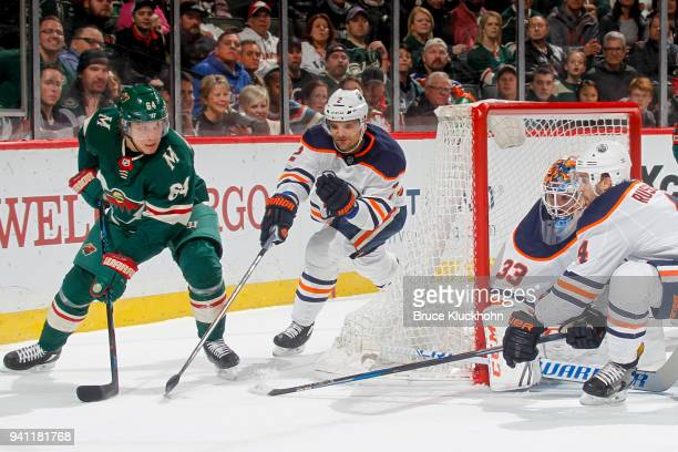 Mikael Granlund of the Minnesota Wild handles the puck with Andrej Sekera Cam Talbot and Kris Russell of the Edmonton Oilers defending during the...