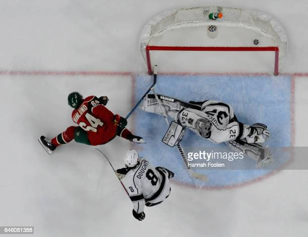 Mikael Granlund of the Minnesota Wild scores the gamewinning goal Jonathan Quick and Drew Doughty of the Los Angeles Kings in overtime of the game on...