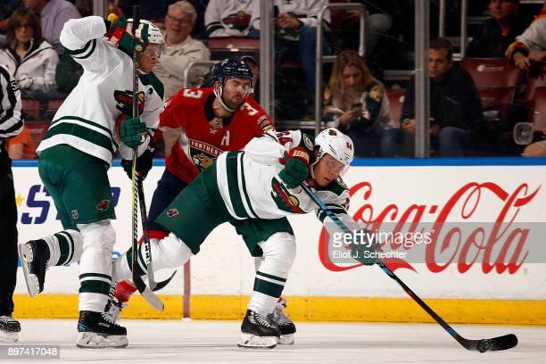 Mikael Granlund of the Minnesota Wild skates for possession against Keith Yandle of the Florida Panthers at the BBT Center on December 22 2017 in...
