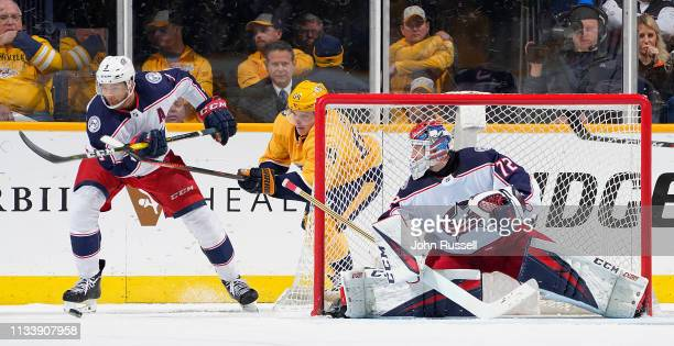 Mikael Granlund of the Nashville Predators battles for the puck behind the net against Seth Jones as Sergei Bobrovsky of the Columbus Blue Jackets...