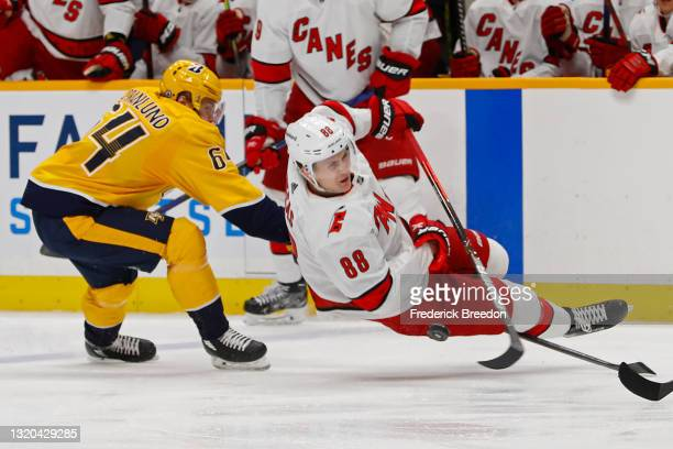 Mikael Granlund of the Nashville Predators trips Martin Necas of the Carolina Hurricanes during the second period in Game Six of the First Round of...