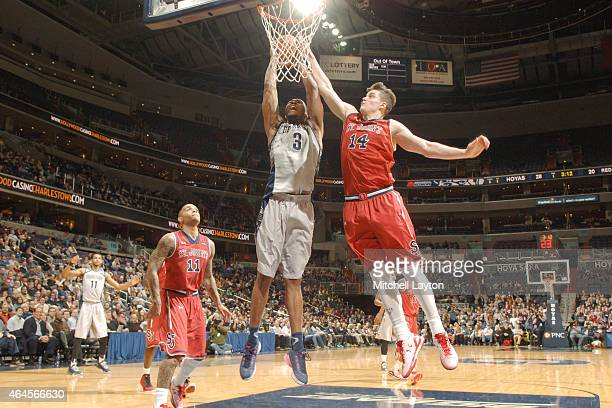 Mikael Hopkins of the Georgetown Hoyas pulls down a rebound over Amar Alibegovic of the St John's Red Storms during a college basketball game at the...