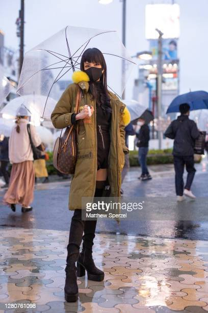 Mikael is seen on the street wearing army green with yellow faux fur down jacket Louis Vuitton bag black face mask thigh high heeled boots during the...
