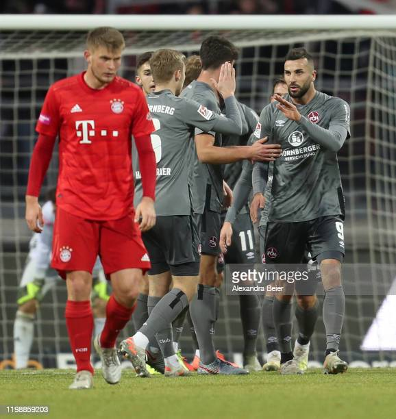 Mikael Ishak and teammates of 1. FC Nuernberg celebrate their fourth goal as Lars Lukas Mai of FC Bayern Muenchen reacts during a friendly match...