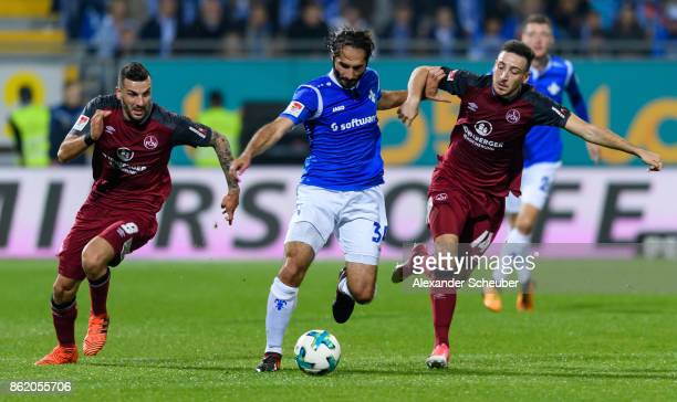 Mikael Ishak of Nuernberg and Kevin Moehwald of Nuernberg challenges Hamit Altintop of Darmstadt during the Second Bundesliga match between SV...