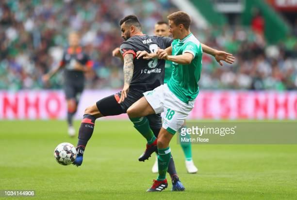 Mikael Ishak of Nuernberg and Niklas Moisander of Werder Bremen battle for possession during the Bundesliga match between SV Werder Bremen and 1. FC...