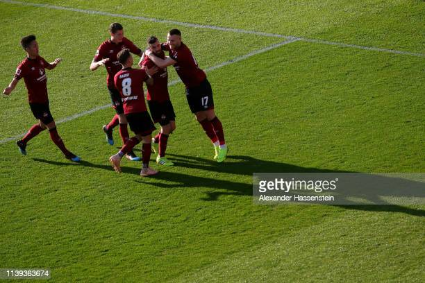 Mikael Ishak of Nuernberg celebrates scoring the opening goal with his team mates during the Bundesliga match between 1 FC Nuernberg and FC Augsburg...
