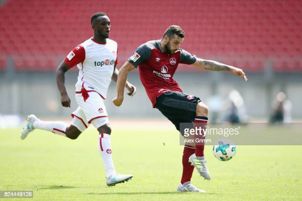 Mikael Ishak of Nuernberg is challenged by Osayamen Osawe of Kaiserslautern during the Second Bundesliga match between 1 FC Nuernberg and 1 FC...