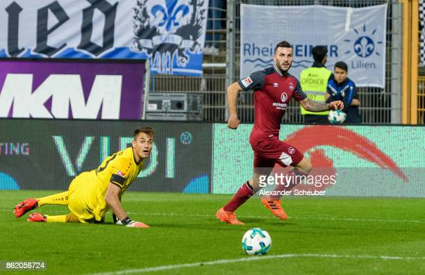 Mikael Ishak of Nuernberg scores the second goal for his team against Joel Mall of Darmstadt during the Second Bundesliga match between SV Darmstadt...