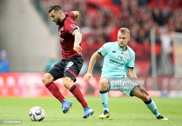 Mikael Ishak of Nuernburg and Daniel Brosinski of FSV Mainz battle for the ball during the Bundesliga match between 1 FC Nuernberg and 1 FSV Mainz 05...