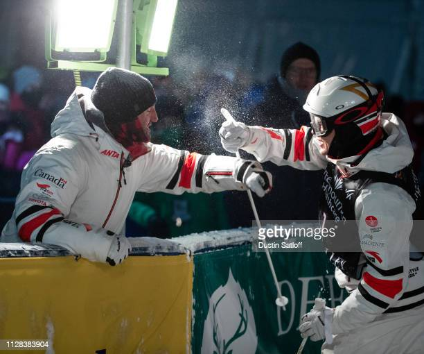 Mikael Kingsbury of Canada celebrates with a coach after his second run during the Men's Moguls Final of the FIS Freestyle Ski World Championships on...