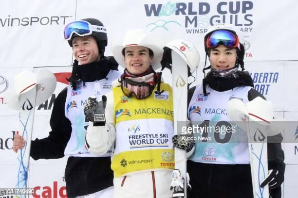Mikael Kingsbury of Canada poses for photos after winning a men's moguls World Cup event in Calgary Canada on Jan 12 alongside runnerup Walter...