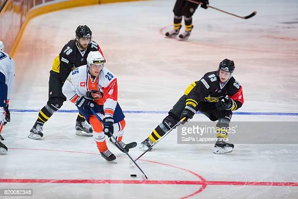Mikael Kuronen and Eetu Koski of Lappeenranta challenges Philip Holm of Vaxjo during the Champions Hockey League Round of 16 match between SaiPa...