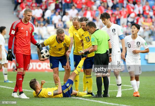 Mikael Lustig of Sweden is helped for his cramps by Gustav Svensson while referee Joel Aguilar of Salvador looks on during the 2018 FIFA World Cup...