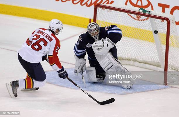 Mikael Samuelsson of the Florida Panthers shoots the puck past Ondrej Pavelec of the Winnipeg Jets for the winning goal during a shootout in NHL...