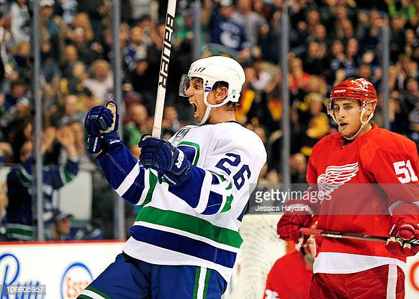 Mikael Samuelsson of the Vancouver Canucks celebrates a goal while Valtteri Filppula of the Detroit Red Wings looks on at Rogers Arena on November 6...