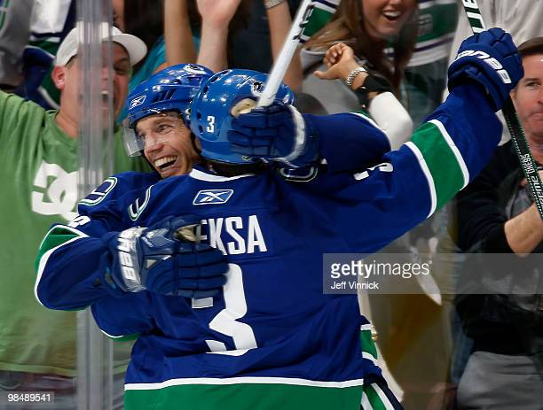 Mikael Samuelsson of the Vancouver Canucks is congratulated by teammate Kevin Bieksa after scoring the overtime winning goal in Game One of the...
