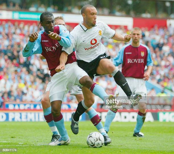 Mikael Silvestre of Manchester United battles for the ball with Jlloyd Samuel of Aston Villa during the FA Barclaycard Premiership match between...