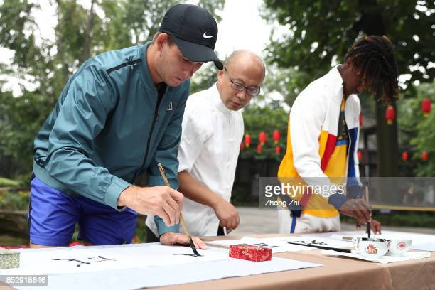 Mikael Ymer of Sweden and Jared Donaldson of the United States practice calligraphy with a master during 2017 ATP Chengdu Open at Wangjianglou Park...