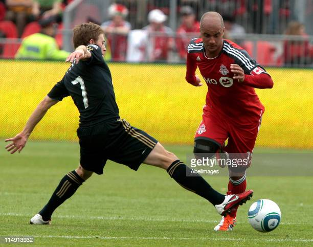 Mikael Yourassowsky of Toronto FC gets tripped up by Brian Carroll of Philadelphia Union during MLS action at BMO Field May 28, 2011 in Toronto,...