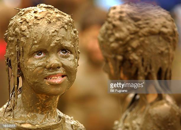 Mikaela Pierce from Livonia Michigan stands caked in mud with her cousin Desiree Lucas during Wayne County's Annual Mud Day July 9 2002 in Westland...