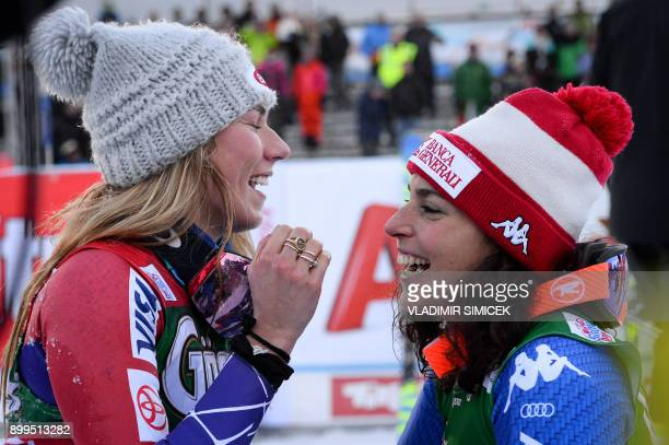 Mikaela Shiffrin of the US laughs with Federica Brignone of Italy as they celebrate after winning the women's giant slalom event of the FIS Ski World...