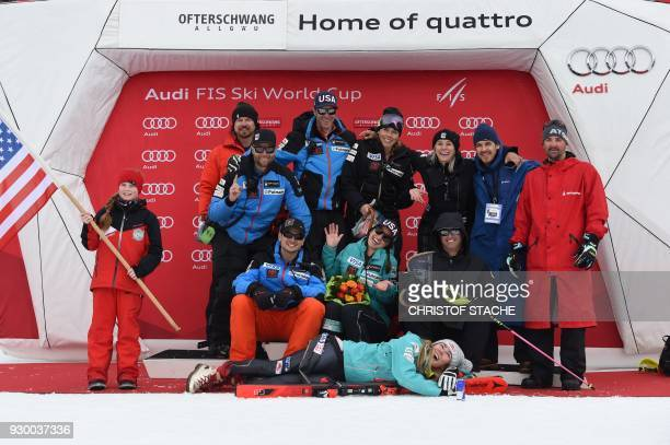 US Mikaela Shiffrin poses with her team and staff members after winning the FIS World Cup Women's Slalom event in Ofterschwang southern Germany on...