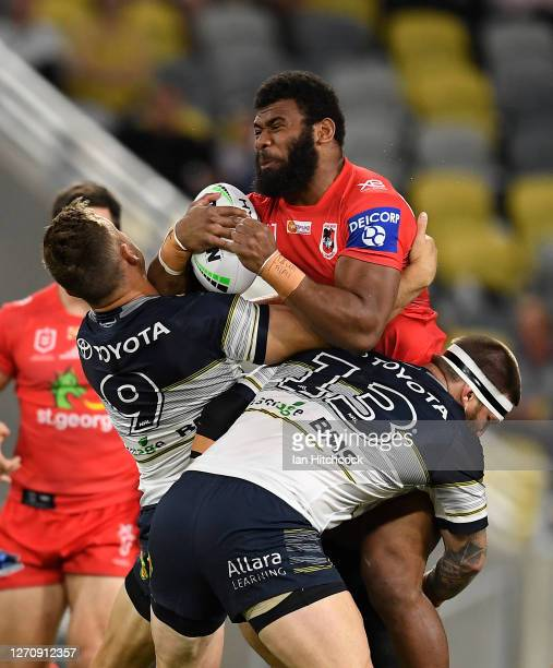 Mikaele Ravalawa of the Dragons is tackled by Josh McGuire and Reuben Cotter of the Cowboys during the round 17 NRL match between the North...