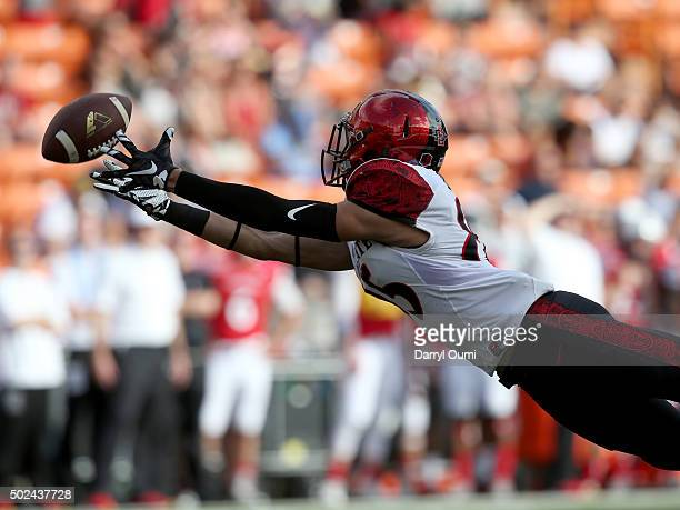 Mikah Holder of the San Diego State Aztecs extends but is unable to make the catch against the Cincinnati Bearcats at Aloha Stadium on December 24...