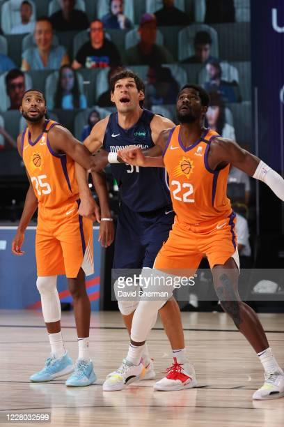 Mikal Bridges and Deandre Ayton of the Phoenix Suns fight for position against Boban Marjanovic of the Dallas Mavericks the Dallas Mavericks on...