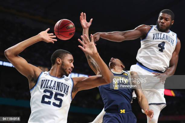 Mikal Bridges and Eric Paschall of the Villanova Wildcats defend Charles Matthews of the Michigan Wolverines in the first half during the 2018 NCAA...