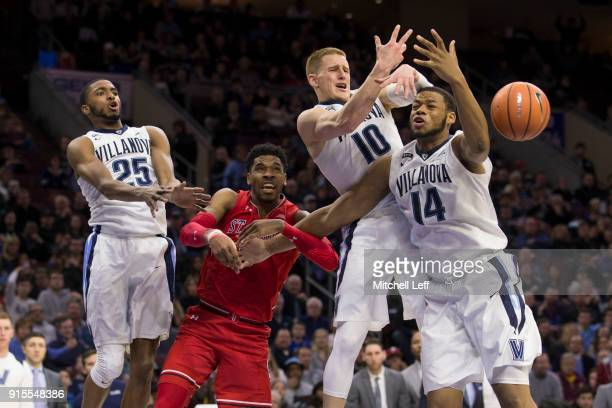 Mikal Bridges Donte DiVincenzo and Omari Spellman of the Villanova Wildcats reach for the ball along with Justin Simon of the St John's Red Storm in...