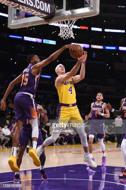 Mikal Bridges of the Phoenix Suns blocks the ball against Alex Caruso of the Los Angeles Lakers during the game during Round 1, Game 3 of the 2021...