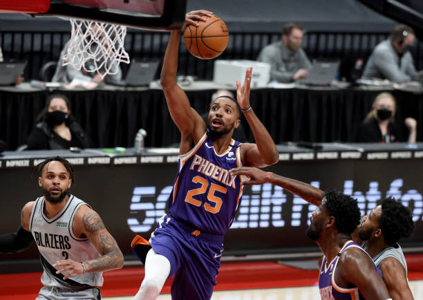 Mikal Bridges of the Phoenix Suns drives to the basket alongside Gary Trent Jr. #2 of the Portland Trail Blazers during the first quarter of the game...