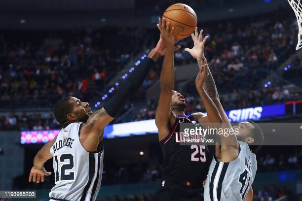 Mikal Bridges of the Phoenix Suns handles the ball against LaMarcus Aldrige and Trey Lyles of the San Antonio Spurs during a game between San Antonio...
