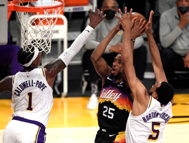 Mikal Bridges of the Phoenix Suns shoots againsst Kentavious Caldwell-Pope and Talen Horton-Tucker of the Los Angeles Lakers during the first half at...