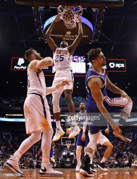 Mikal Bridges of the Phoenix Suns slam dunks the ball over Raul Neto of the Philadelphia 76ers during the first half of the NBA game at Talking Stick...