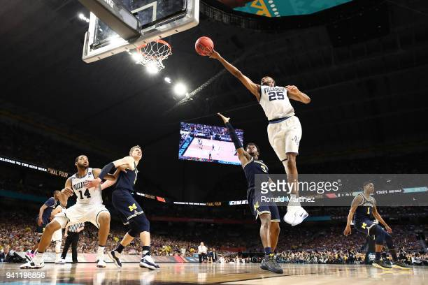 Mikal Bridges of the Villanova Wildcats drives to the basket against Zavier Simpson of the Michigan Wolverines in the second half during the 2018...